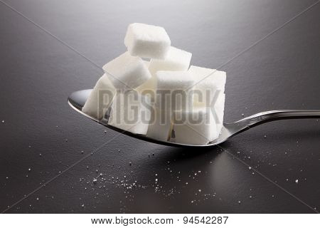 big or super size spoon with pile of cube white sugar