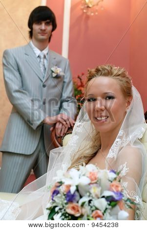 Wedding portrait of bride and groom. Groom in background looking into camera.