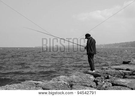 GENEVA - SEP 11: man fishing at Geneva lake on September 11, 2014 in Geneva, Switzerland. Geneva is the second most populous city in Switzerland and is the most populous city of Romandy