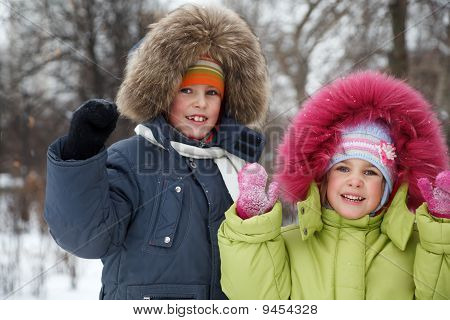 Brother and sister smiling looking into camera in winter forest.