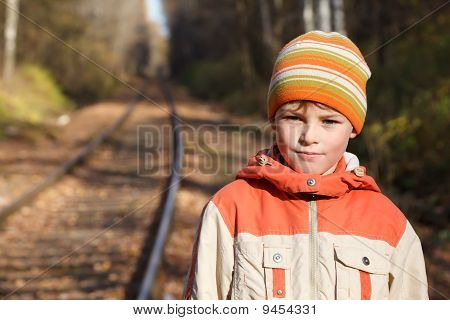 Portrait of boy autumn sunny day on railway.