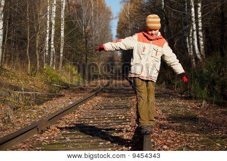 Boy walks along railway in the autumn in a sunny day.