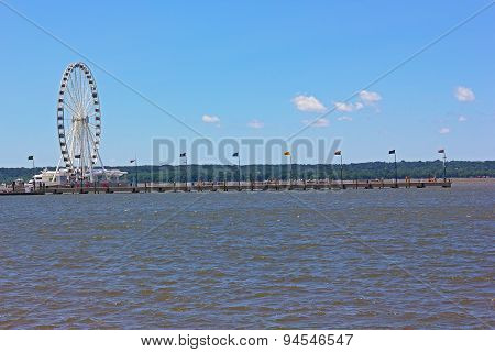Ferris wheel of National Harbor and a long pier in Maryland, USA.