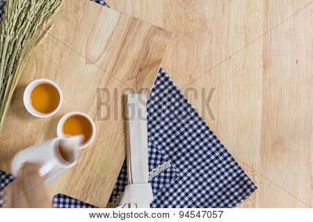 Pouring Tea Into Cup Of Tea On Wood Texture Background