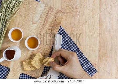 Taking Biscuit On Wood Texture Background