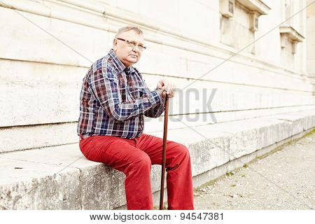 Portrait of mature man in glasses, plaid shirt, wooden walking stick sitting and looking aside