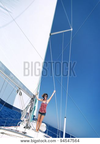Happy cheerful woman having fun on sailboat in sunny day, enjoying summer adventure in sea cruise, active summertime vacation