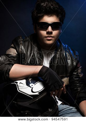Portrait of handsome stylish teen boy posing in the studio over dark blue background, wearing bikers outfit and holding helmet in hands