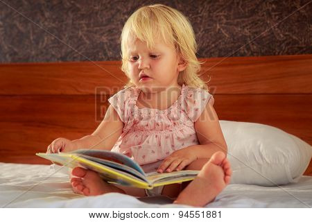 Little Girl In Pink Sits On Sofa And Looks At Book Cover