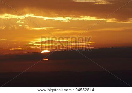 Setting Sun Behind A Cloud