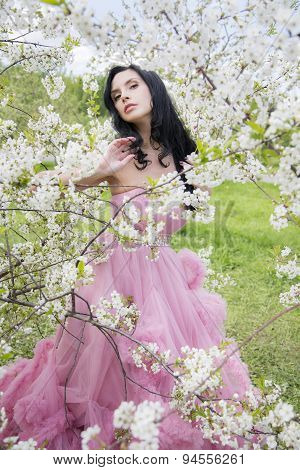 Young woman in the garden of apple blossom