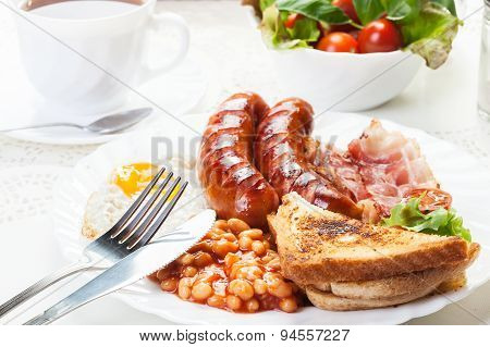 Full English Breakfast With Bacon, Sausage, Fried Egg And Baked
