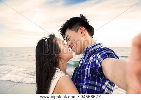 Couple Taking Self Portrait Photos With Smart Phone On The Beach