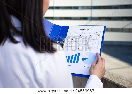 Business Plan Concept - Woman Holding Folder With Different Charts