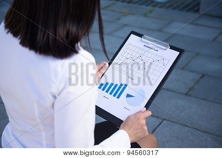 Business Concept - Woman Holding Clipboard With Different Charts