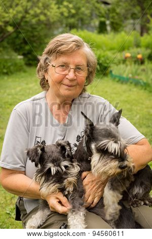 Senior Woman Hugs Her Two Pets, Black And Silver Miniature Schnauzer Dog In Countryside