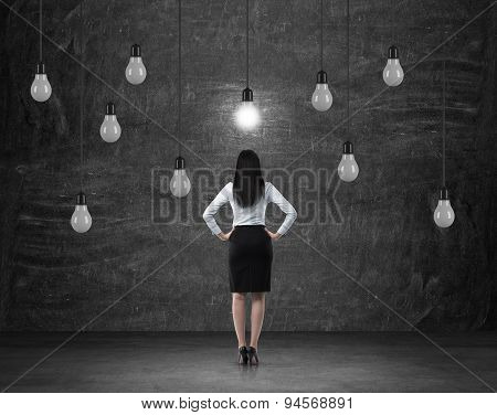 Rear View Of The Brunette Woman In Formal Clothes Who Is Surrounded By Light Bulbs As A Symbol Of Th