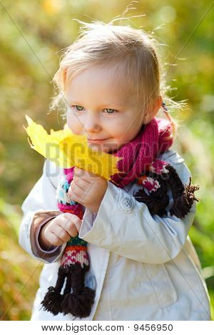 Toddler Girl With Yellow Leaf