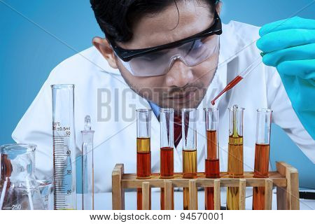 Scientist Combining The Chemical Fluid