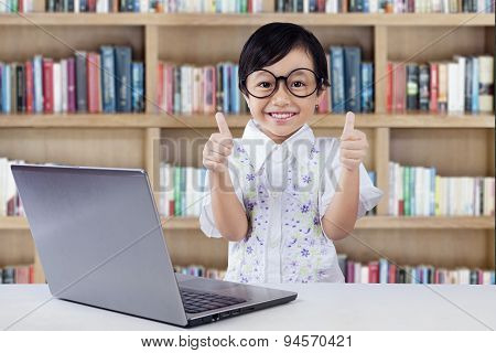 Satisfied Little Student Shows Thumbs Up In Library