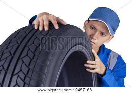 Technician Examining A Tire