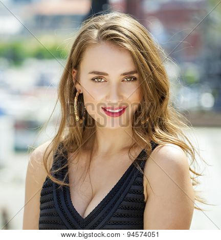 Portrait close up of young happy beautiful woman, on background summer street
