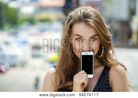 Young woman covers her face screen smartphone on a background summer street