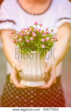 Young girl holding vase with fresh spring flowers