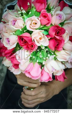 Two Hand Holding Colorful Bunch Rose