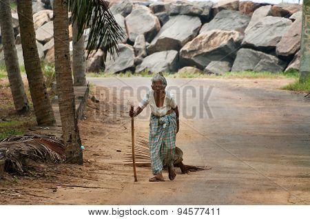 Elderly Woman Walking Along The Road In The Fishing Village