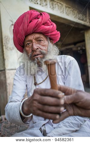 GODWAR REGION, INDIA - 12 FEBRUARY 2015: Elderly Rabari tribesman with traditional turban, clothes and long beard hands out chillum. Rabari or Rewari are an Indian community in the state of Gujarat.
