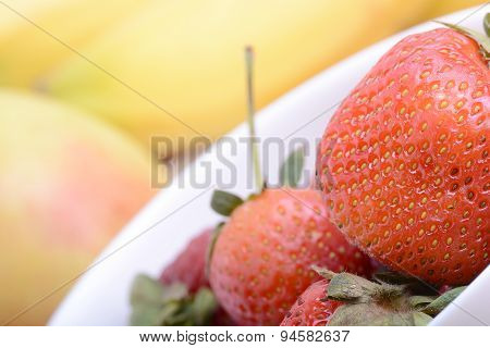 Fruits. Arrangement Of Various Fresh Ripe Fruits: Bananas, Apple And Strawberries Closeup