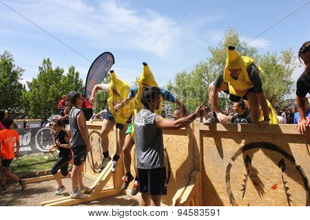Group Of People Dresssed As Bananas Jumping Over An Obstacle