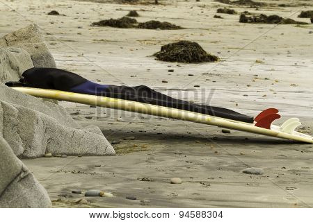 Surfboard Leaning On Rocks At Beach