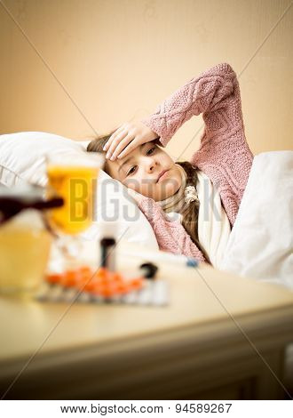 Sick Girl Lying In Bed Next To Table Table With Medicines