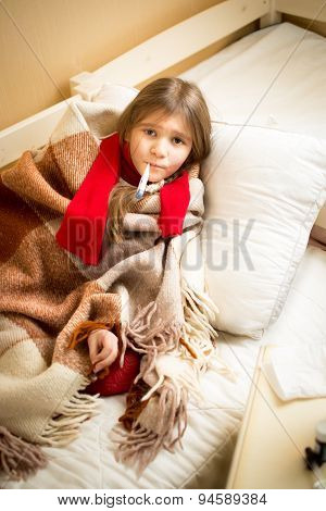 Sick Girl Lying In Bed With Teddy Bear And Measuring Temperature