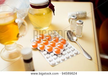 Closeup Of Pills In Blister And Honey Jar On Bedside Table