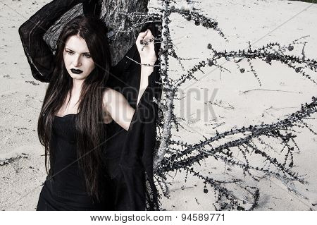 Young Woman In A Black Clothes Near The Tree
