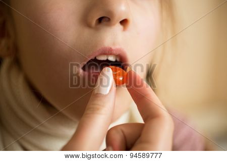 Macro Shot Of Little Sick With Flu Girl Taking Pill In Mouth