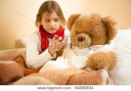 Girl Playing And Measuring Teddy's Bear Temperature With Thermometer