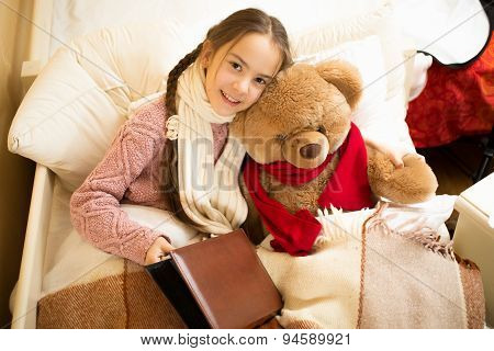 Cute Smiling Girl Reading Book With Teddy Bear In Bed