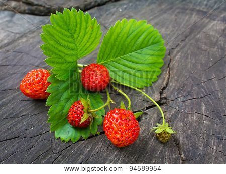 Ripe Strawberries And Green Leaves On A Wooden Background