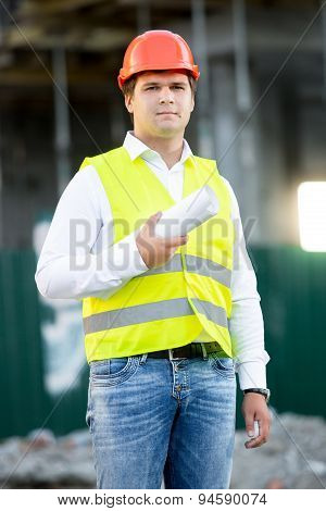 Architect In Hardhat Posing With Blueprints Against Scaffolding