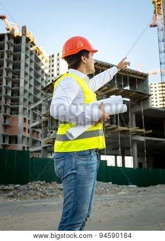 Engineer In Hardhat And Safety Jacket Checking Building Site