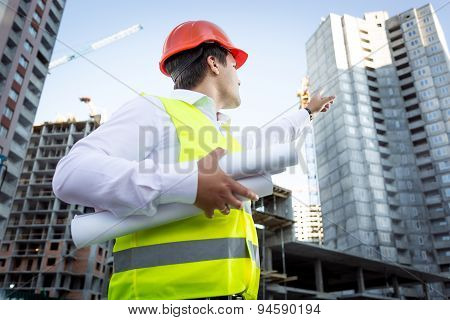 Portrait Of Foreman With Blueprints Pointing Hand At Building