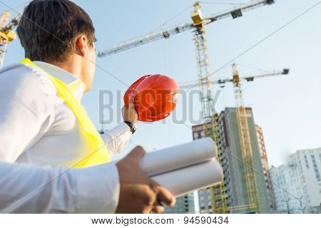 Closeup Of Engineer Posing On Building Site With Orange Hardhat