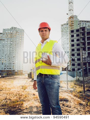 Toned Photo Of Engineer Posing Against Building Site At Sunset