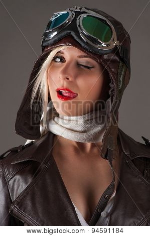 woman in aviator helmet winks and licking lips