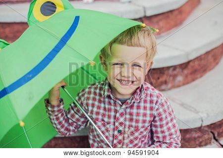 Adorable toddler boy with green frog umbrella. Outdoors portrait