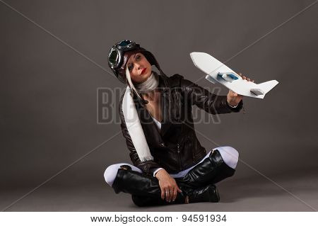 woman in aviator helmet playing with toy airplane
